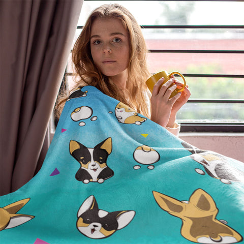 model with a corgi pattern blanket pulled up over her shoulder, holding a mug