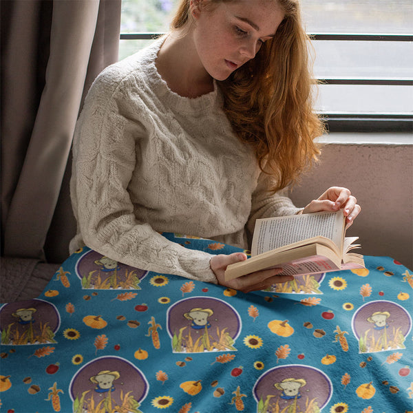 Model sitting near a window reading a book underneath scarecrow blanket