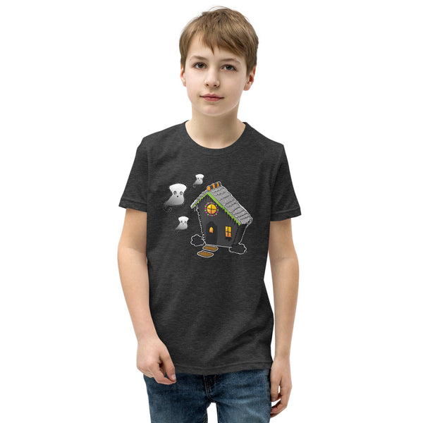 Boy wearing Ghost and Haunted Gingerbread House kids' tee in dark gray heather. There's a black gingerbread house with gray roof, orange and black  gummies on the roof, and three marshmallow ghosts floating to the left of the house.