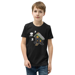 Boy wearing Ghost and Haunted Gingerbread House kids' tee in black. There's a black gingerbread house with gray roof, orange and black  gummies on the roof, and three marshmallow ghosts floating to the left of the house.