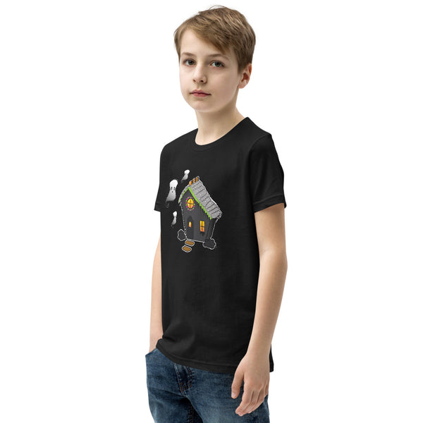 Side view of boy wearing Ghost and Haunted Gingerbread House kids' tee in black. There's a black gingerbread house with gray roof, orange and black  gummies on the roof, and three marshmallow ghosts floating to the left of the house.