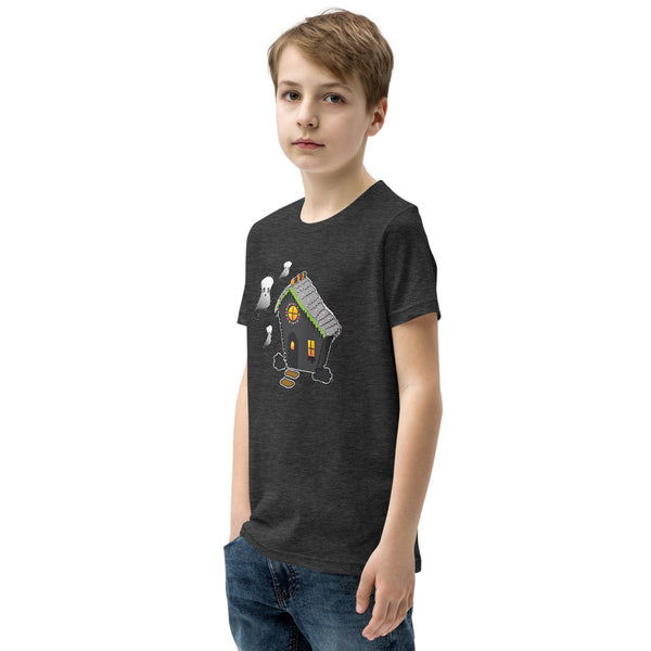 Side view of boy wearing Ghost and Haunted Gingerbread House kids' tee in dark gray heather. There's a black gingerbread house with gray roof, orange and black  gummies on the roof, and three marshmallow ghosts floating to the left of the house.