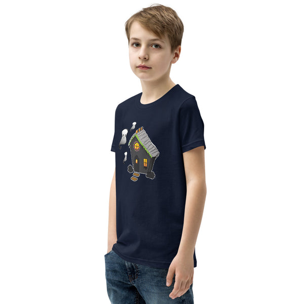 Side view of boy wearing Ghost and Haunted Gingerbread House kids' tee in navy. There's a black gingerbread house with gray roof, orange and black  gummies on the roof, and three marshmallow ghosts floating to the left of the house.