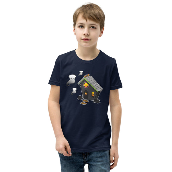 Boy wearing Ghost and Haunted Gingerbread House kids' tee in navy. There's a black gingerbread house with gray roof, orange and black  gummies on the roof, and three marshmallow ghosts floating to the left of the house.