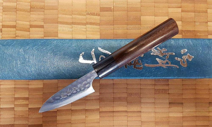 A Masakage Anryu Aogami Petty 75mm Japanese chef knife resting on its blue presentation box with a chopping board background.