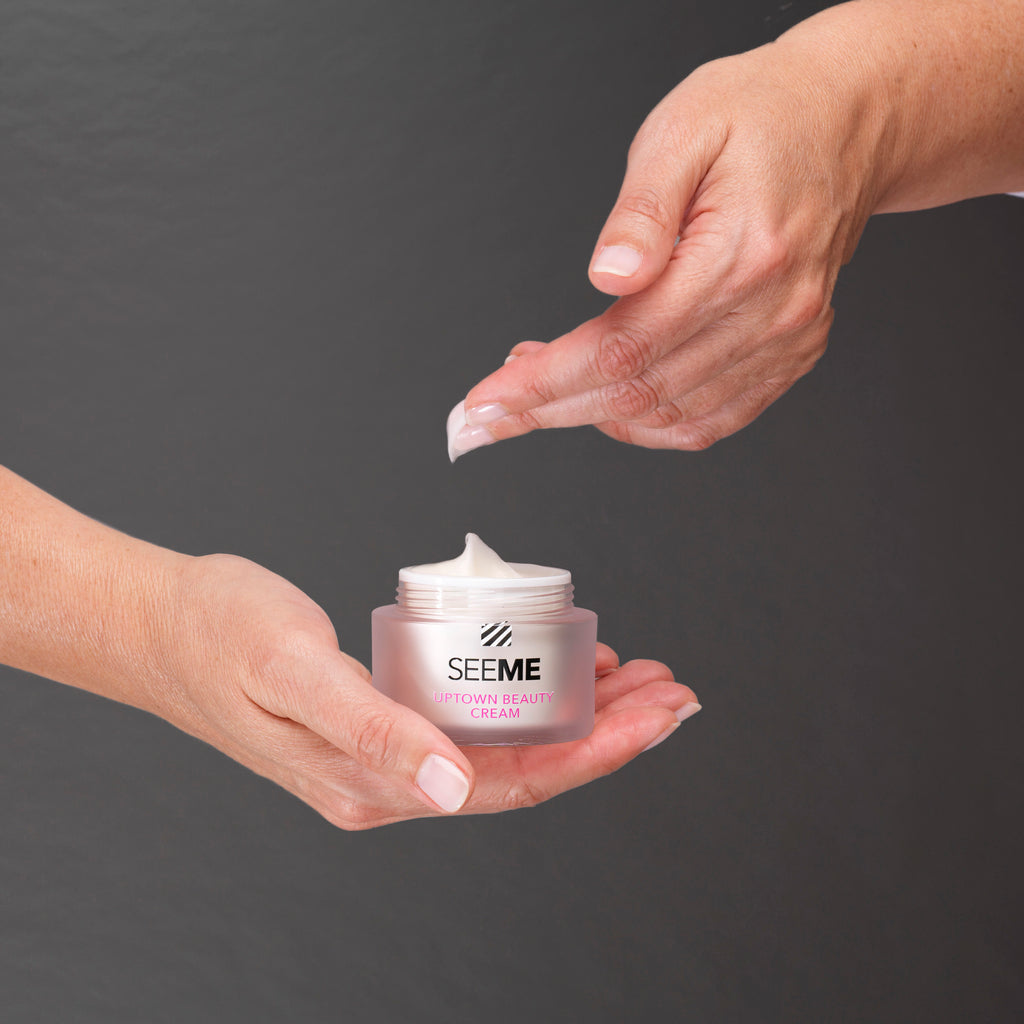SeeMe Uptown Beauty Cream with SeeMe complex. Image of woman dipping the light airy moisturizer from the jar she is cradling in her hand.