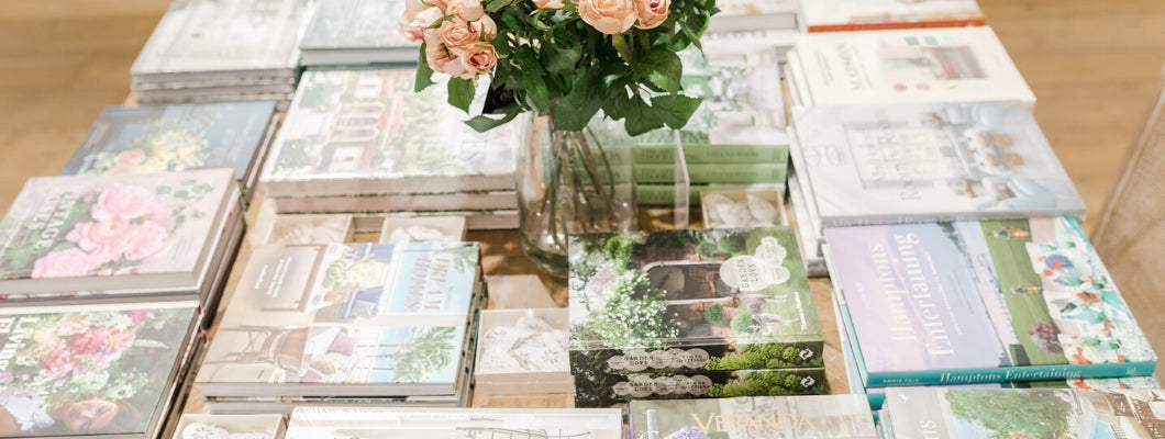 Pile of floral and interior design coffee table books on top of french country style square table with flowers in the middle
