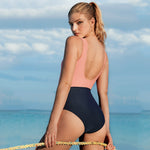 Back view of a model wearing a pink and black two-tone one-piece swimsuit with an open back and full coverage bottoms. Background is the ocean.