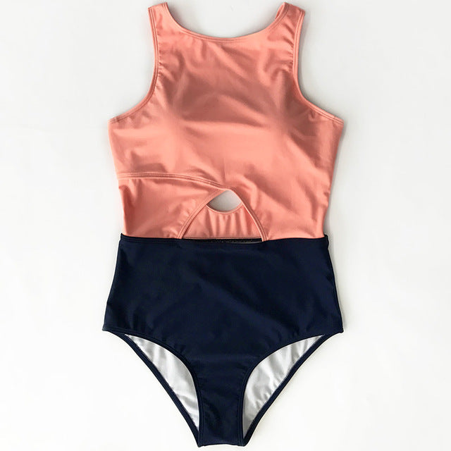 Pink and black two tone one-piece swimsuit with a cutout on the stomach laid flat. Background is solid white.