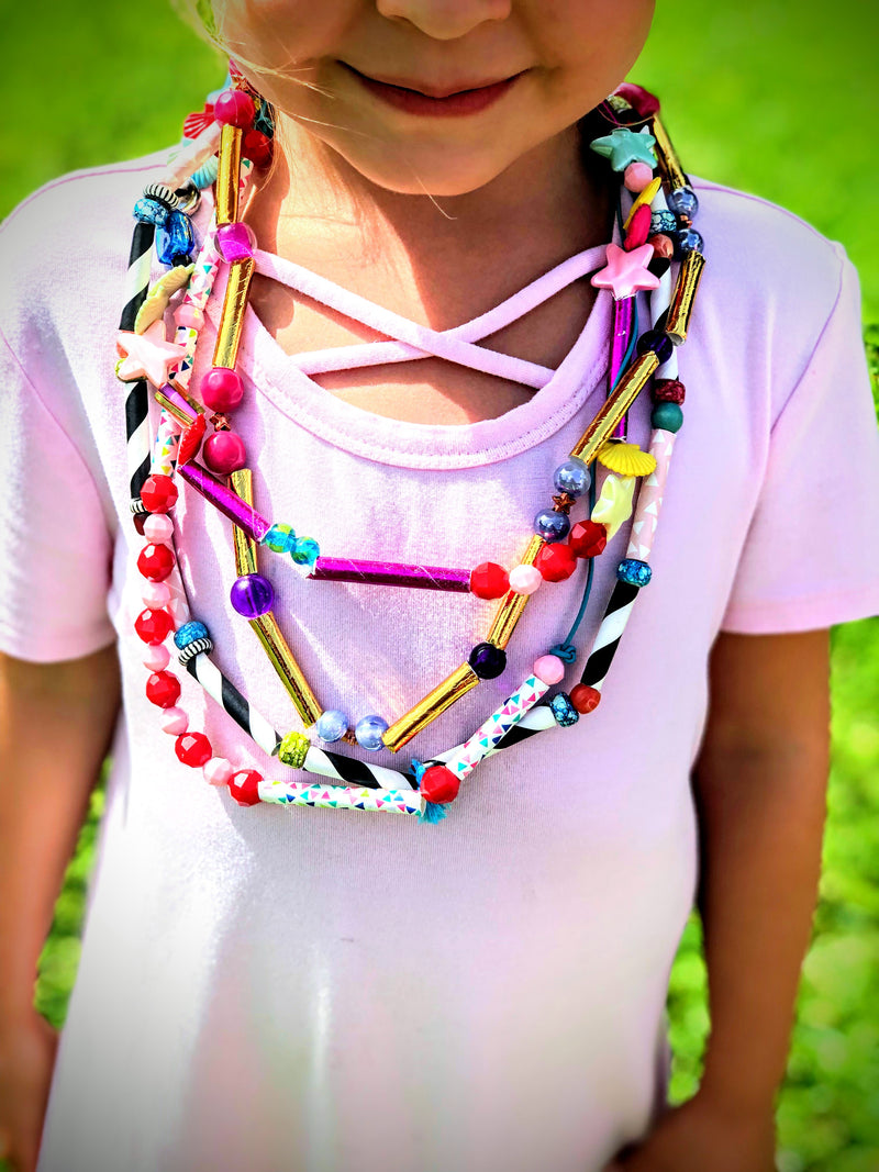 Little girl in a pink shirt wearing a straw and bead diy necklace