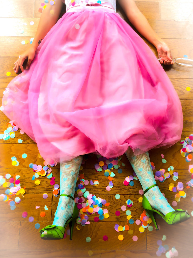 Woman in green shoes and pink dress tired from too much partying