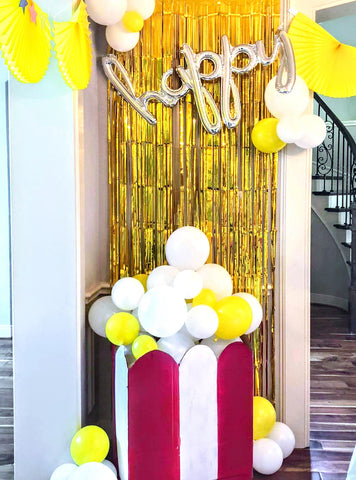Giant DIY popcorn bag made from balloons with a gold streamer backdrop party setup