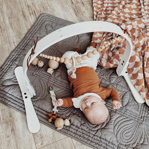 Baby boy playing on quilted playmat