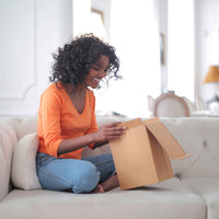 Cheerful african american woman unpacking a parcel.
