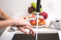 Hands being washed at a sink with fruit bowl in the background.