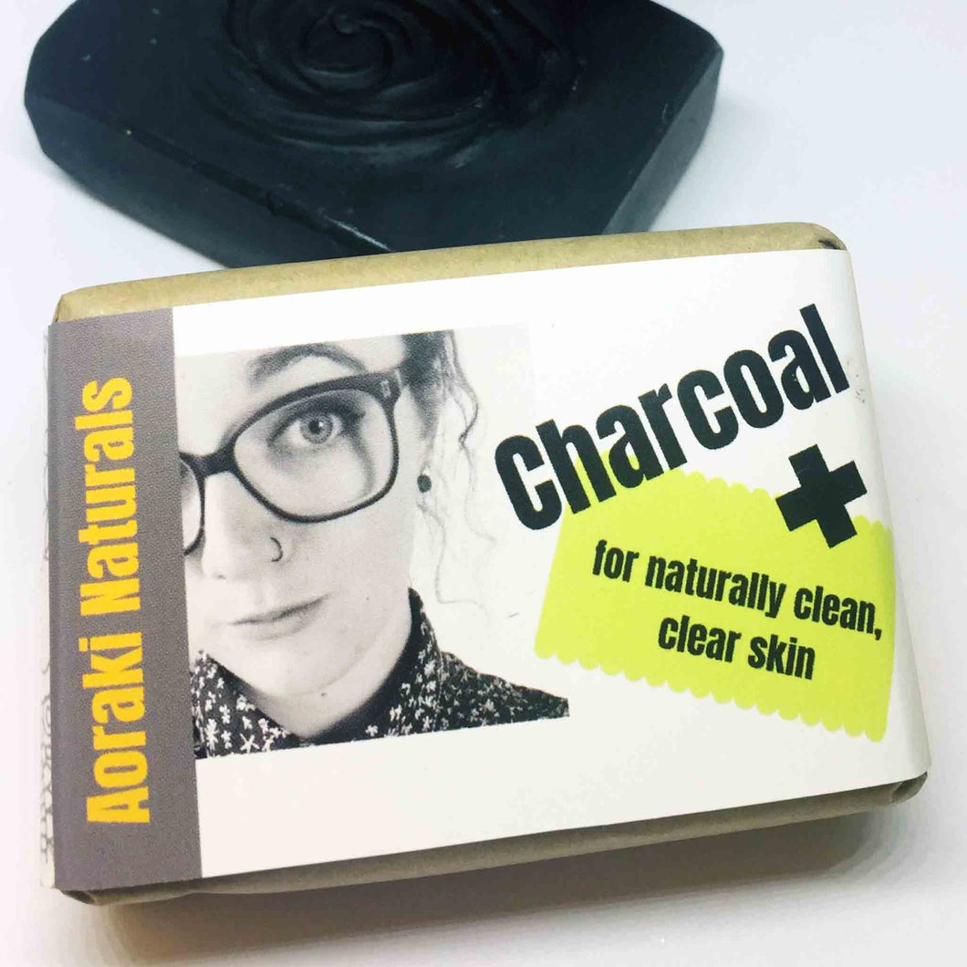 Charcoal plus face wash packaging with solid bar in the background.