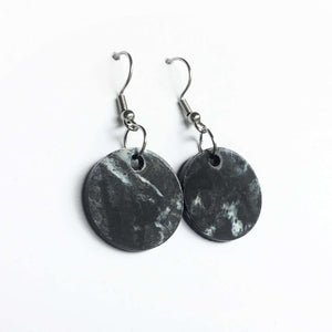 Black and white circular plastic earrings made from 3D printer waste.