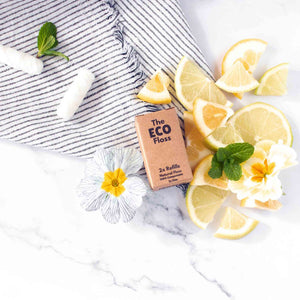 Compostable dental floss refill in cardboard packaging surrounded by flowers and lemons.
