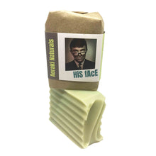 His face cleansing bar for shaving and pampering your face. Packaged product seen here standing atop a ready to use bar of soap.