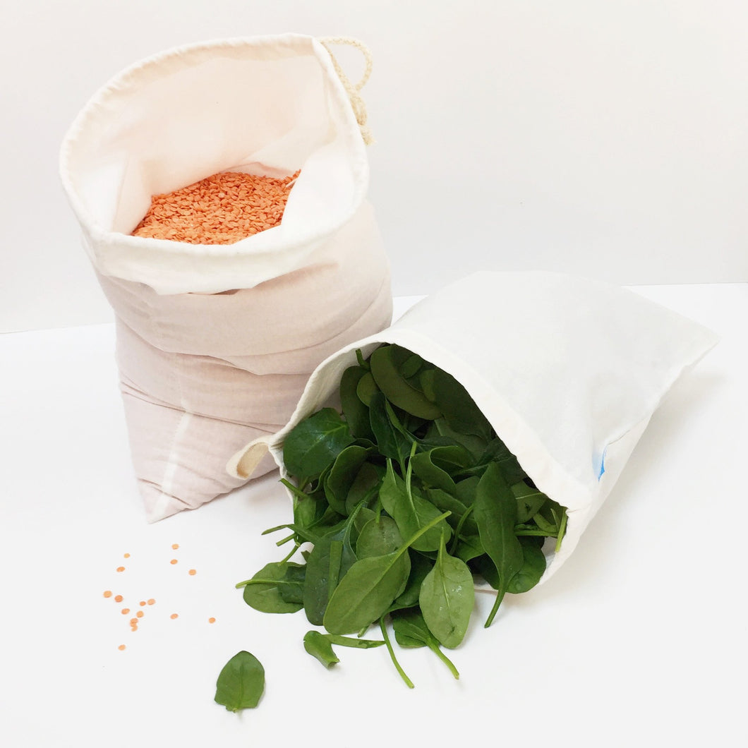 Two loot bags - one containing spinach leaves and the other full of red lentils.
