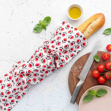 Organic reusable bread bag in pohutukawa design with French bread and tomatoes.