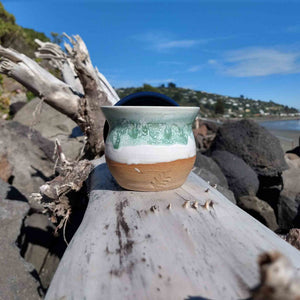 Curvy ceramic coffee cup without its navy lid sitting on driftwood.