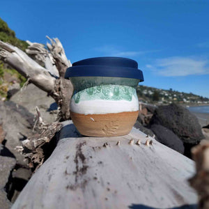 Curvy ceramic coffee cup with navy lid sitting on driftwood.