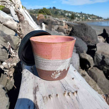 Dark blush ceramic travel cup sitting on driftwood.