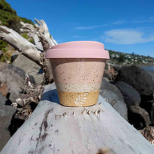 Speckled Pink ceramic coffee cup with pink lid sitting on driftwood.
