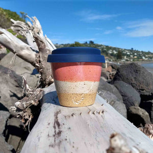 Speckled blush ceramic coffee cup with navy lid sitting on driftwood.