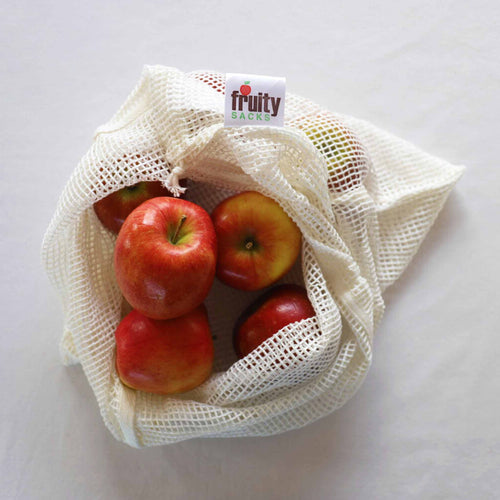 Red apples in a reusable bamboo shopping bag.