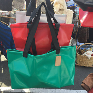 Display of three totes in green, red and grey.