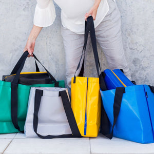 Person holding a selection of totes in various colours.