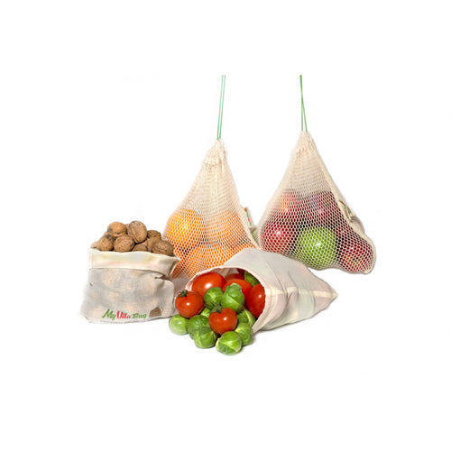 Four organic cotton produce bags containing fruit and nuts