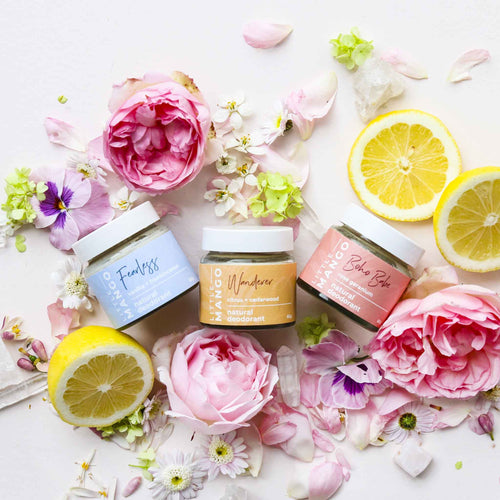 A trio of Little Mango natural and vegan deodorants surrounded by flowers and cut lemons.