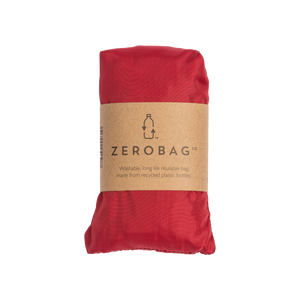Photograph of reusable red grocery bag in pouch with cardboard sleeve