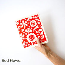 Dish cloth with white flowers on red background design.