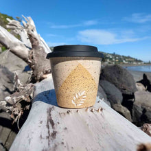 Speckled travel mug with black lid sitting on driftwood.