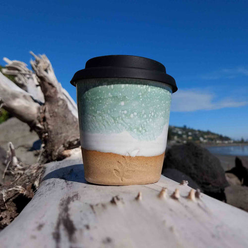 Minty white pottery espresso coffee cup sitting on driftwood.