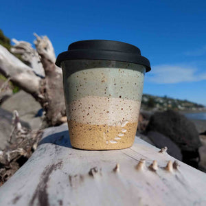 Speckled Mint ceramic espresso travel cup with black silicone lid sitting on driftwood at Sumner Beach, Christchurch, New Zealand.