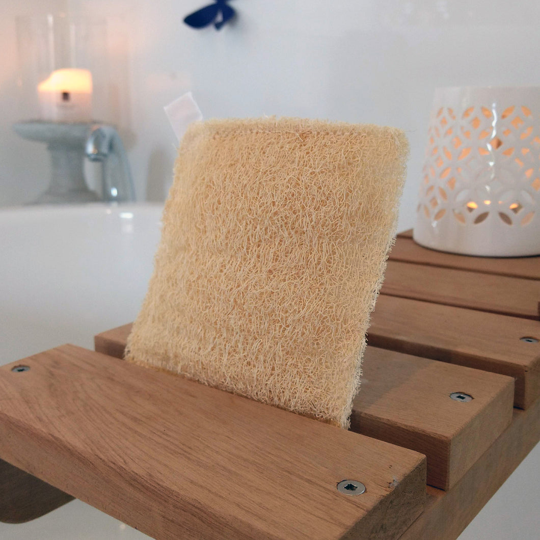 Bath scene with Square Loofah Sponge and two candles burning in the background.