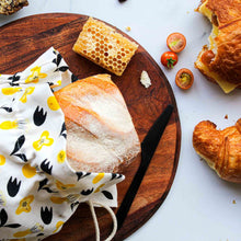 Organic reusable bread bag in yello flower design on benchtop with bread and food.