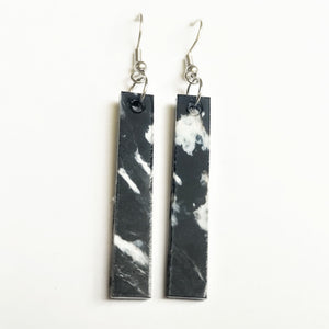 Straight and narrow black and white plastic earrings made from 3D printer waste.