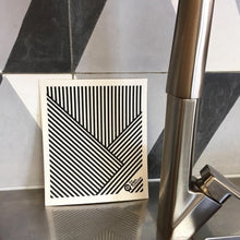 Dish cloth with stripes design and kitchen counter backdrop.