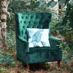 Green armchair with a buttoned back and wooden legs
