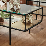 Black framed rectangular glass coffee table with a gold base shelf & glass top shelf