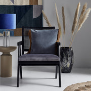 Black wooden armchair with a geometric wicker back and velvet seat pad