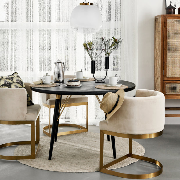 Round black wooden dining table with gold detailing