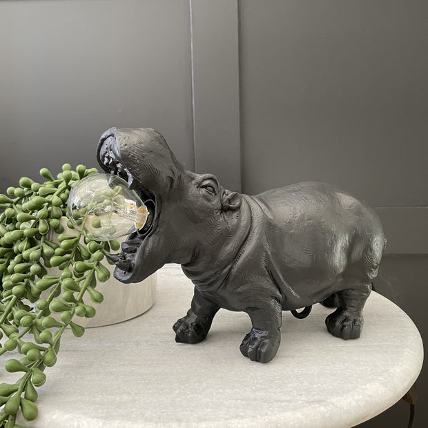 Black hippo table lamp with a bulb in it's mouth