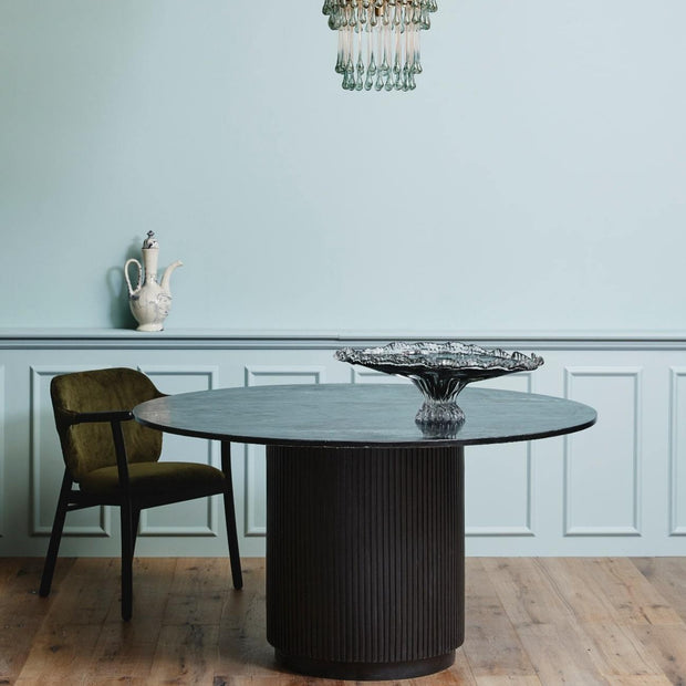 Black round marble dining table with a pillar base